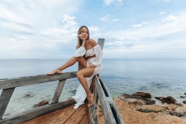 Opalona dziewczyna w seksownej białej sukni siedzi na dziobie zniszczonego statku na plaży