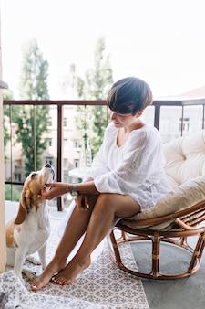 Opalona dziewczyna z eleganckim manicure i pedicure bawiąca się zabawnym psem rasy beagle, który odpoczywa na dywanie