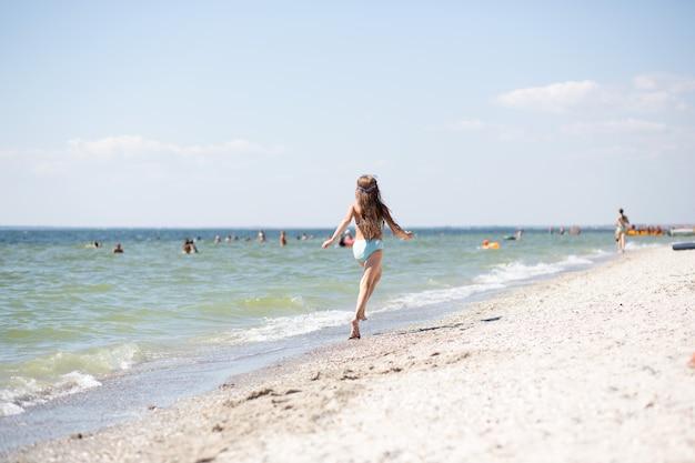 Opalona dziewczynka z długimi włosami w niebieskim stroju kąpielowym wesoło biegnie wzdłuż piaszczystego brzegu w pobliżu morza czarnego, widok z tyłu