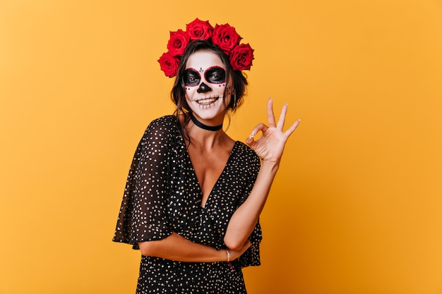Opalona kobieta o śnieżnobiałym uśmiechu pokazuje znak w porządku. zdjęcie młodej damy w pomieszczeniu z makijażem halloween na pomarańczowym tle.