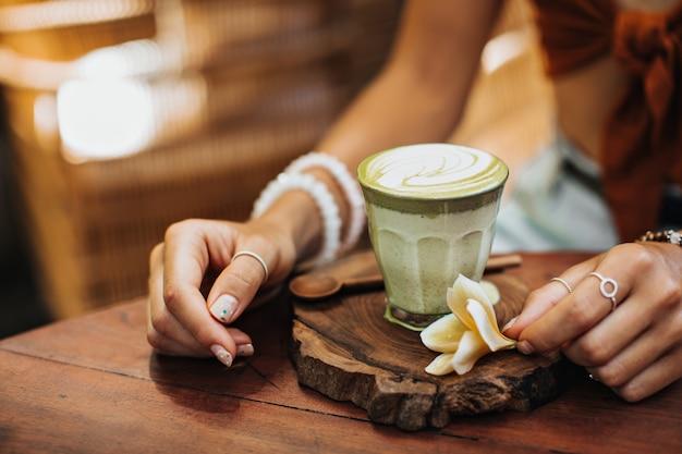Opalona kobieta siedzi w kawiarni i pozuje filiżankę zielonej herbaty matcha z mlekiem