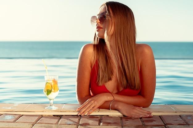 Opalona kobieta w czerwonym bikini w basenie przy koktajlu