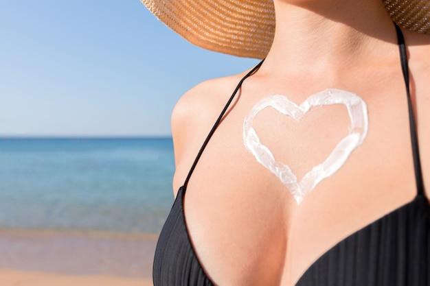 Opalona kobieta z kremem przeciwsłonecznym w kształcie serca na piersi na tle morza.