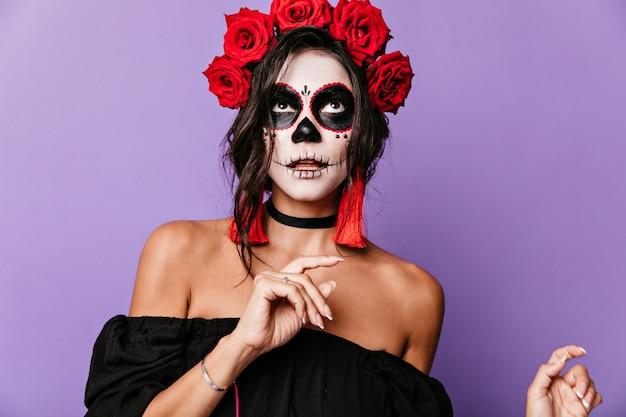 Opalona latynoska zamyślona dama na liliowej ścianie. dziewczyna z ciemnymi kręconymi włosami i różami w nich pozuje z maską szkieletu na twarzy
