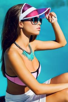 Opalona piękna młoda modelka w różowych stylowych strojach plażowych i jasnych akcesoriach kolorystycznych siedząca w pobliżu basenu. modny portret.