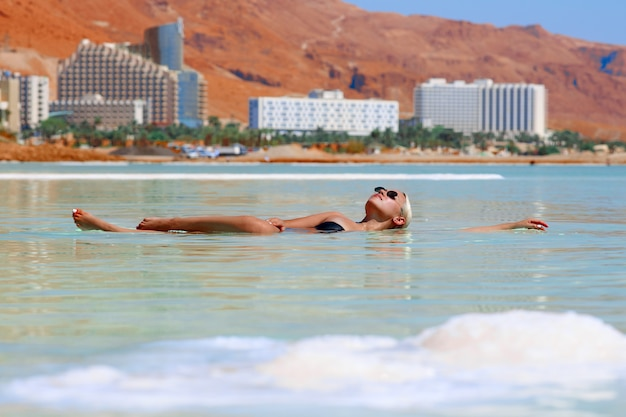 Opalona seksowna blond dziewczyna w czarnym kostiumie kąpielowym i okularach przeciwsłonecznych pływa w wodach morza martwego w izraelu