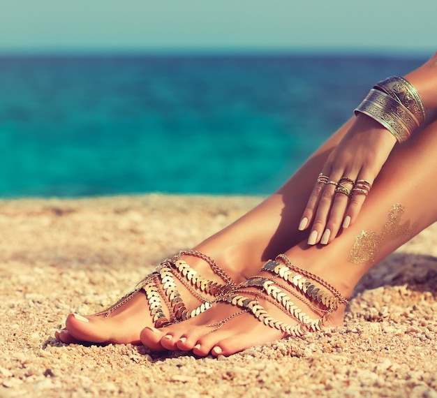 Opalone kobiece nogi i dłoń pokryte biżuterią w stylu boho spoczywają na ciele z morskiego piasku