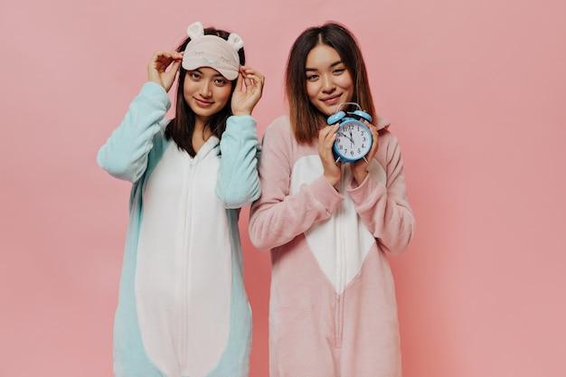 Opalone młode kobiety w piżamach patrzą z przodu, uśmiechają się i pozują na różowej ścianie