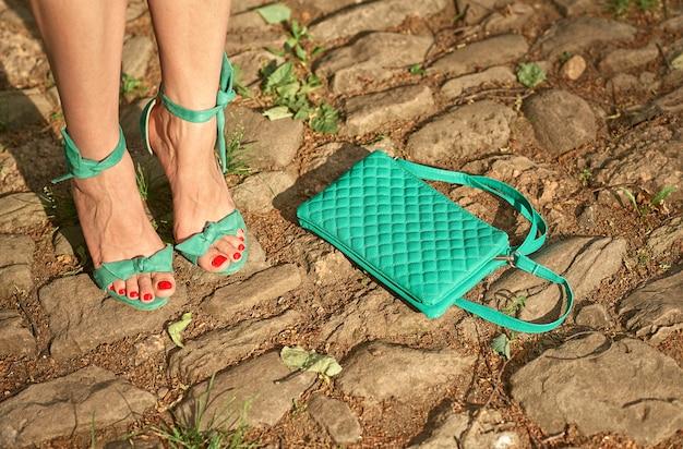 Opalone nogi modelki w sandałach retro z obcasami i damską torebką rzuconą na drogę.
