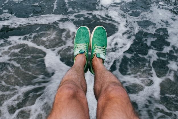 Opalone owłosione, mocne męskie nogi w zielone letnie lekkie tenisówki na abstrakcyjnym wodospadzie w ruchu