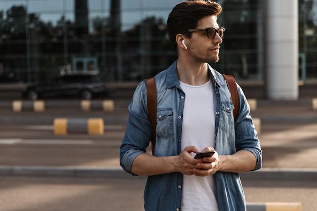 Opalony brunetka mężczyzna w białej koszulce, dżinsowej kurtce i okularach przeciwsłonecznych pozuje na zewnątrz