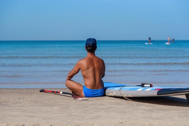 Opalony mężczyzna siedzi na plaży w pobliżu deski surfingowej i patrzy na morze.