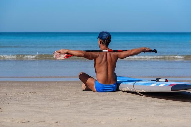 Opalony mężczyzna siedzi na plaży z deską surfingową i wiosłem i patrzy na morze.