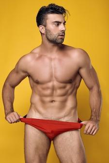 Opalony muskularny mężczyzna ubrany w czerwoną bieliznę na żółto