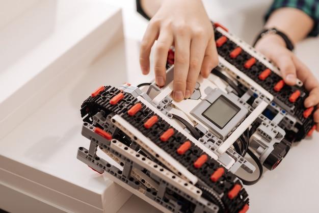 Opanowanie poziomu programowania. utalentowany sumienny i inteligentny chłopiec siedzący w klasie i dotykający urządzenia podczas programowania robota