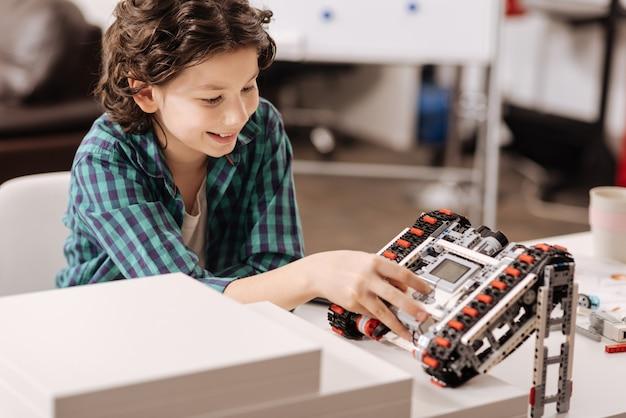 Opanowanie Programowania. Uśmiechnięty Utalentowany Utalentowany Chłopiec Siedzący W Klasie Wyrażający Zadowolenie I Programujący Robota Premium Zdjęcia