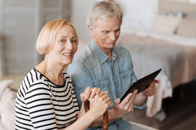 Opanowanie współczesnych technologii. dwie mądre, energiczne starsze osoby spędzają razem czas, oglądając ciekawe filmy na tablecie