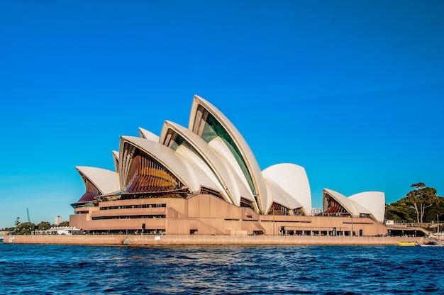 Opera w sydney w pobliżu pięknego morza pod jasnym, błękitnym niebem