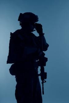 Operacje specjalne korpusu piechoty morskiej stanów zjednoczonych dowodzą najeźdźcą marsoc z bronią. sylwetka morskiego operatora specjalnego na niebieskim tle