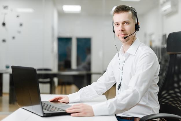 Operator call center odbiera połączenia biznesowe w biurze przez zestaw słuchawkowy online