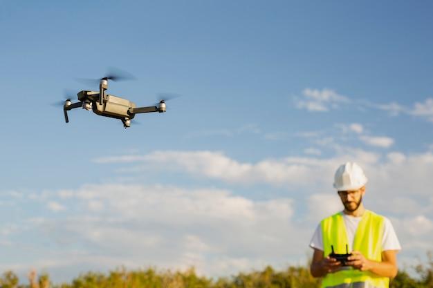 Operator drona pilotujący drona w wiejskim otoczeniu