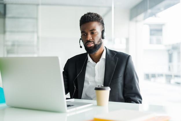 Operator gorącej linii. portret rozochocony afrykański obsługa klienta przedstawiciel z słuchawki w centrum telefonicznym