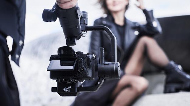 Operator kamery wideo pracujący z dziewczyną modelki na zewnątrz