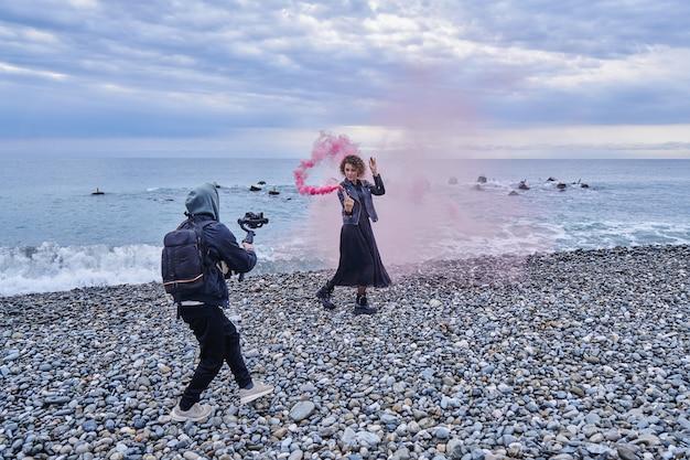 Operator kamery wideo pracujący z dziewczyną modelki nad brzegiem morza z kolorową bombą dymną