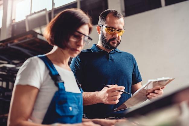 Operator maszyny cnc i inżynier przemysłowy sprawdzający rysunek produktu