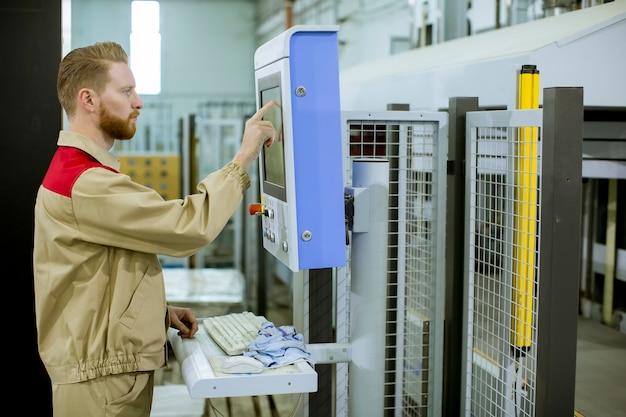 Operator męski naciska przycisk na panelu sterowania na urządzeniach sterujących w zakładzie produkcji mebli