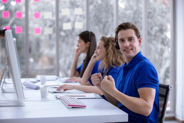 Operator mężczyzna siedzi kciuki do góry przy biurku przed komputerem.