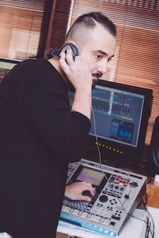 Operator nagrywający ze słuchawkami miksujący niektóre utwory