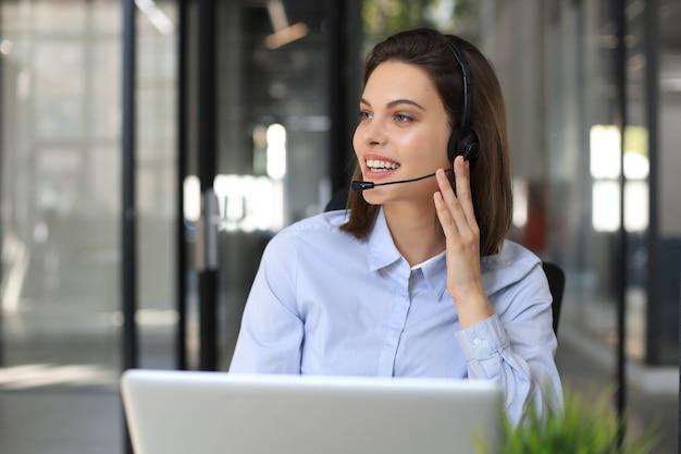 Operator obsługi klienta kobieta z zestawu słuchawkowego i uśmiechnięty.
