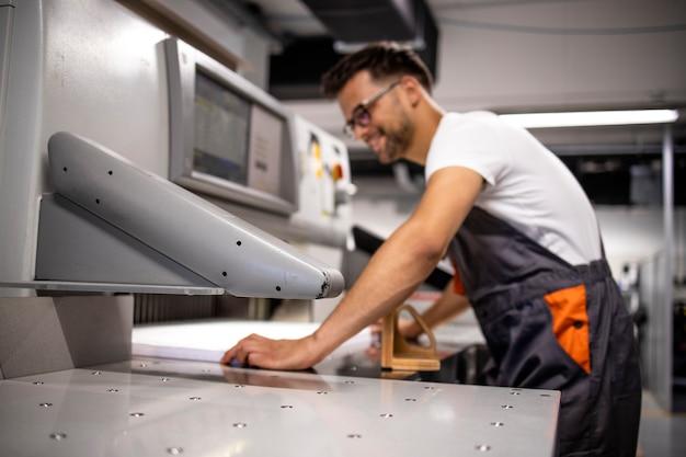 Operator pracujący na maszynie do cięcia papieru w drukarni.