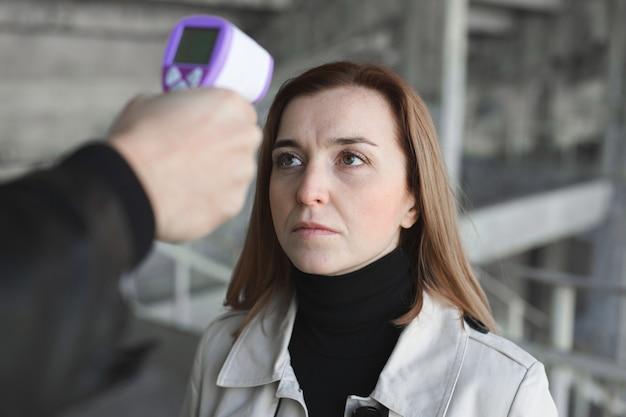 Operator sprawdza gorączkę za pomocą cyfrowego termometru