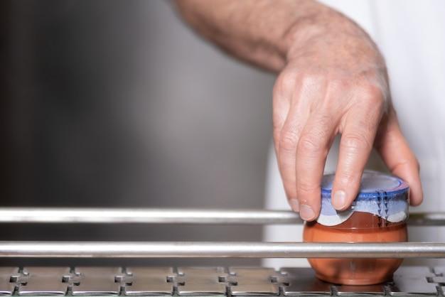 Operator sprawdza jakość na końcowym etapie napełniania jogurtem produkcyjnym