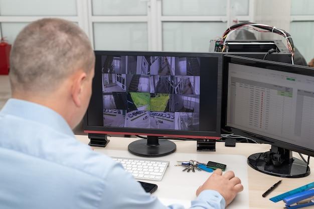 Operator systemu monitoringu cctv monitorujący kamery wideo w pomieszczeniu ochrony