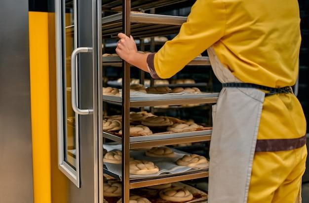 Operator z tacami na ciasto chlebowe, gotowe do umieszczenia w fabrycznych piecach. chleb piekarniczy produkcja fabryczna żywności ze świeżych produktów.