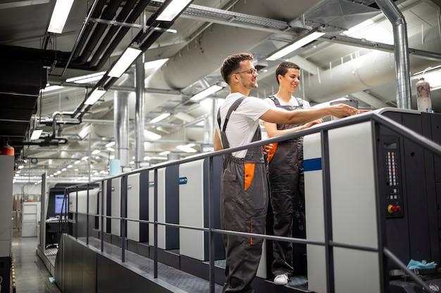 Operatorzy maszyn drukarskich kontrolujący proces drukowania i kontrolę jakości.