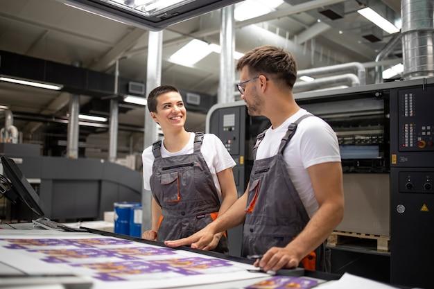 Operatorzy maszyn drukarskich sprawdzający jakość grafiki i kolorystykę w drukarni.