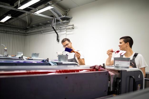 Operatorzy maszyn drukarskich współpracujący z farbami w drukarni.