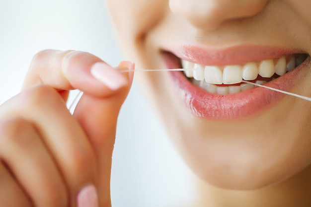 Opieka dentystyczna. kobieta z pięknym uśmiechem za pomocą nici do zębów. obraz
