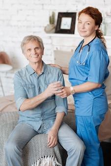 Opieka domowa. wykształcony kompetentny pracownik medyczny podaje pacjentowi szklankę wody, aby poczuł się lepiej podczas cotygodniowych konsultacji w domu