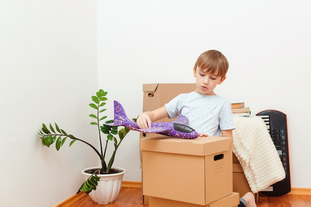 Opieka i ochrona rodziny. przeprowadzka dnia. szczęśliwy chłopiec zabawy w przeprowadzce dnia. mieszkanie młodej rodziny z dzieckiem. rodzina wprowadza się do nowego mieszkania. dziecko marzy o nowym domu.