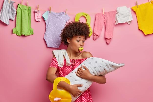 Opieka nad dziećmi, pojęcie macierzyństwa. zajęta mama z kręconymi włosami obejmuje noworodka, pozuje z akcesoriami dla niemowląt, zajęta karmiąca piersią