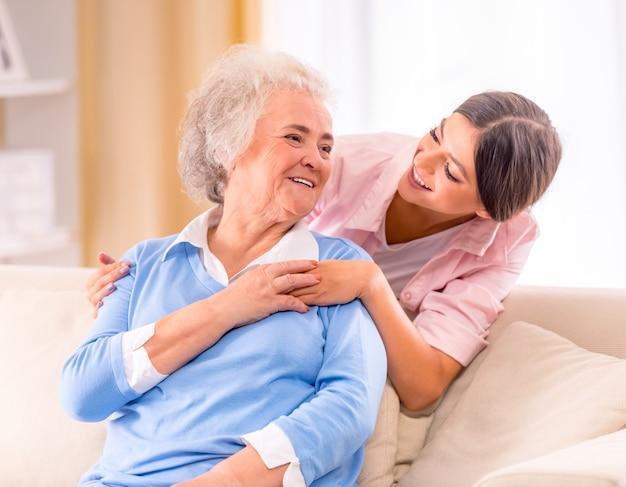 Opieka nad starszą kobietą w domu siedzi na kanapie.
