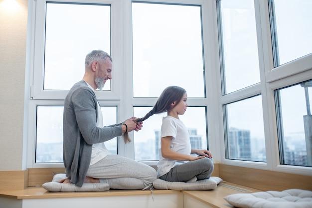 Opieka. profil uśmiechniętego siwowłosego taty robi włosy swojej ciemnowłosej córce w domowych ubraniach siedzącej na parapecie w domu