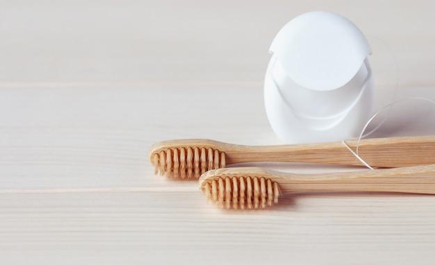 Opieka stomatologiczna i koncepcja zrównoważonego życia - drewniana szczoteczka do zębów i nić dentystyczna