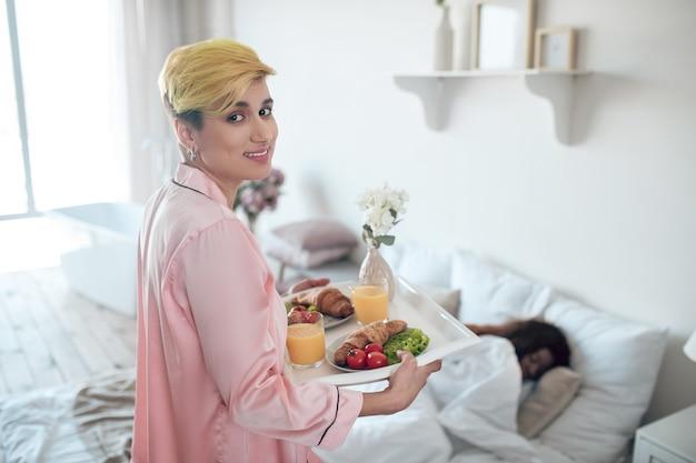 Opieka. uśmiechnięta młoda dorosła kobieta w różowych ubraniach z tacą śniadaniową dla ciemnoskórej śpiącej dziewczyny w sypialni
