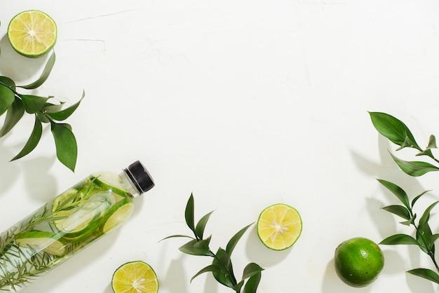 Opieka zdrowotna, fitness, koncepcja diety zdrowego odżywiania. świeża chłodna woda cytrynowa z rozmarynem, koktajl, napój detoksykujący, lemoniada w szklanym słoiku. jasny widok z góry na płaskiej świeckiej tle